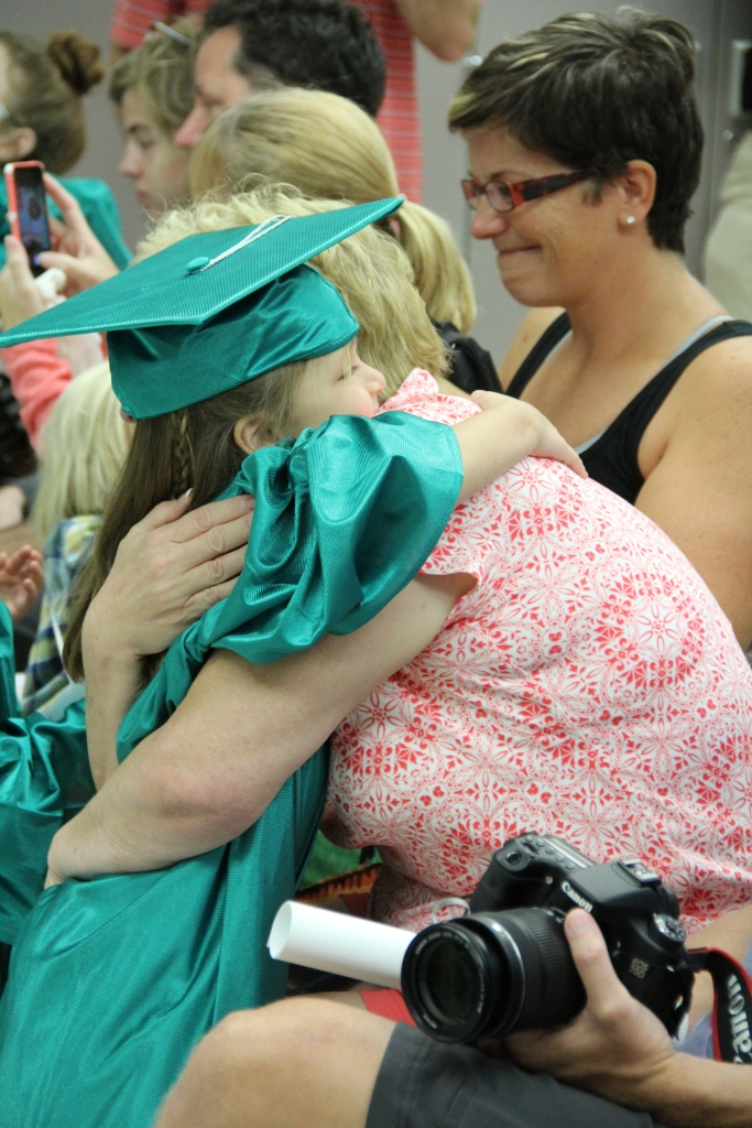 A Mini Mustang celebrates graduation with a hug from mom.