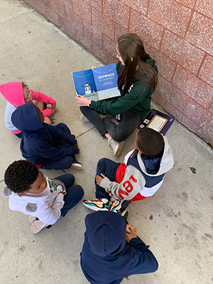 HIgh schooler reading to elementary student.